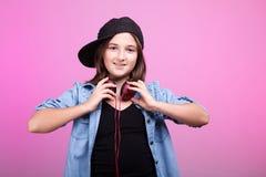 Δροσερό κορίτσι εφήβων που φορά τα ακουστικά και ένα καπέλο Στοκ εικόνες με δικαίωμα ελεύθερης χρήσης