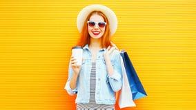 Δροσερό κορίτσι με ένα φλυτζάνι καφέ, τσάντες αγορών, καπέλο αχύρου στο πορτοκάλι Στοκ Εικόνα