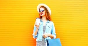 Δροσερό κορίτσι με ένα φλυτζάνι καφέ, τσάντες αγορών που φορά ένα καπέλο αχύρου Στοκ φωτογραφία με δικαίωμα ελεύθερης χρήσης