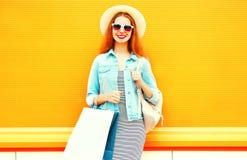 Δροσερό κορίτσι με τις τσάντες αγορών, καπέλο αχύρου στο πορτοκάλι Στοκ εικόνες με δικαίωμα ελεύθερης χρήσης