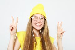 Δροσερό κορίτσι μόδας στα ακουστικά που ακούει τη μουσική που φορά το κίτρινες καπέλο και την μπλούζα στοκ φωτογραφίες