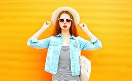 Δροσερό κορίτσι σε ένα καπέλο αχύρου στο πορτοκαλί υπόβαθρο Στοκ Εικόνα