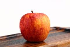Δροσερό κόκκινο μήλο στον ξύλινο δίσκο που απομονώνεται στο άσπρο υπόβαθρο Στοκ Εικόνα