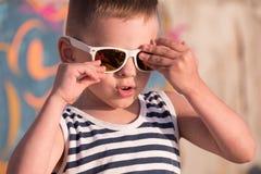 Δροσερό μικρό παιδί με τα γυαλιά ηλίου και πουκάμισο ναυτικών στο υπόβαθρο γκράφιτι Στοκ εικόνα με δικαίωμα ελεύθερης χρήσης