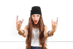 Δροσερό νέο κορίτσι στο μαύρο καπέλο που παρουσιάζει σημάδι των κέρατων Στοκ Εικόνες
