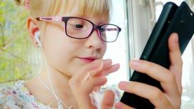 Δροσερό ξανθό κορίτσι 6 έτη χρήσης του τηλεφώνου Στα ακουστικά της, γελά, θετικές συγκινήσεις στον ήλιο Κάθεται απόθεμα βίντεο