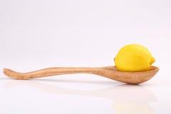 Δροσερό οργανικό φρέσκο ώριμο λεμόνι στο ξύλινο κουτάλι στο λευκό Στοκ Φωτογραφία