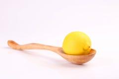 Δροσερό οργανικό φρέσκο ώριμο λεμόνι στο ξύλινο κουτάλι στο λευκό Στοκ Εικόνες