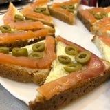 Δροσερό σάντουιτς με τα κόκκινες ψάρια και τις ελιές σε ένα άσπρο πιάτο στοκ εικόνα