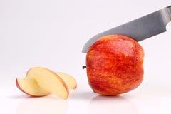Δροσερό φρέσκο κόκκινο μήλο που τεμαχίζεται με το μαχαίρι κουζινών στο λευκό Στοκ εικόνες με δικαίωμα ελεύθερης χρήσης