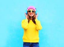 Δροσερό χαμογελώντας κορίτσι μόδας αρκετά που ακούει τη μουσική στα ακουστικά που φορούν το ζωηρόχρωμο ρόδινο καπέλο, τα κίτρινα  Στοκ φωτογραφία με δικαίωμα ελεύθερης χρήσης