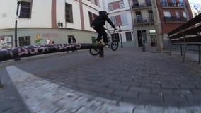 Δροσερό BMX bicycler που κάνει τις διαφορετικά περιστροφές και τα τεχνάσματα στο ποδήλατο στο αστικό περιβάλλον φιλμ μικρού μήκους