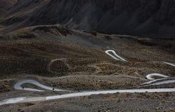 Δρόμοι βρόχων με τους ποδηλάτες στις βαθιές κοιλάδες του εδάφους αγριοτήτων Ladakh, Ινδία Στοκ Εικόνες