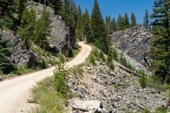 Δρόμος αμμοχάλικου ρύπου που περνά από τα βουνά στο Αϊντάχο bounders στοκ εικόνες