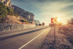 Δρόμος ασφάλτου και οδικό σημάδι στα βουνά στην ανατολή Στοκ Εικόνες