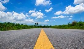 Δρόμος ασφάλτου και σύννεφα στο μπλε ουρανό Στοκ Φωτογραφίες