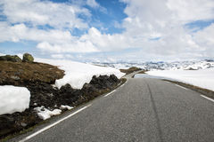 Δρόμος ασφάλτου μέσω των βουνών με πολύ χιόνι, καλοκαίρι Νορβηγία Εθνική διαδρομή Aurlandsfjellet τουριστών Στοκ Εικόνες