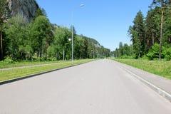 Δρόμος ασφάλτου με τα πεζοδρόμια και τους φωτεινούς σηματοδότες σε ένα ηλιόλουστο καλοκαίρι δ στοκ εικόνες