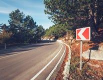 Δρόμος ασφάλτου με το οδικό σημάδι στο δάσος στην ανατολή Στοκ Φωτογραφία