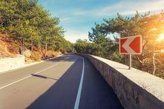 Δρόμος ασφάλτου με το οδικό σημάδι στο δάσος στην ανατολή Στοκ εικόνες με δικαίωμα ελεύθερης χρήσης