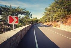 Δρόμος ασφάλτου στο δάσος φθινοπώρου στην ανατολή και το οδικό σημάδι Στοκ Εικόνες