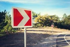 Δρόμος ασφάλτου στο δάσος φθινοπώρου στην ανατολή και το οδικό σημάδι Στοκ φωτογραφία με δικαίωμα ελεύθερης χρήσης