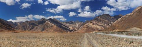 Δρόμος βουνών χώρας: τα τεντώματα διαδρομής κατά μήκος των υψηλών βουνών της ερήμου μεταξύ των χρωματισμένων καφετιών βουνών με τ Στοκ Εικόνες