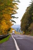 Δρόμος εθνικών οδών φθινοπώρου με το ημι φορτηγό και τα κίτρινα δέντρα Στοκ Εικόνα