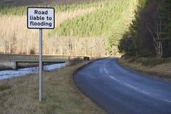Δρόμος εκτεθειμένος στην πλημμύρα του σημαδιού οδικής ασφάλειας από τον ποταμό στην αγροτική επαρχία στοκ φωτογραφίες