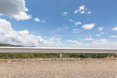 Δρόμος και εμπόδιο με το υπόβαθρο και το σύννεφο βροχής μπλε ουρανού που κινούνται στο φως του ήλιου απογεύματος Στοκ φωτογραφία με δικαίωμα ελεύθερης χρήσης