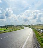 Δρόμος και χαμηλά σύννεφα στο μπλε ουρανό Στοκ Εικόνες