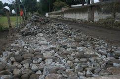 Δρόμος κυβόλινθων κάτω από την κατασκευή που παρουσιάζει τις πέτρες, wheelbarrow και ατελές τμήμα του δρόμου Στοκ Εικόνες