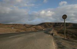 Δρόμος μέσω της ερήμου με τη στάση λεωφορείου Στοκ εικόνα με δικαίωμα ελεύθερης χρήσης