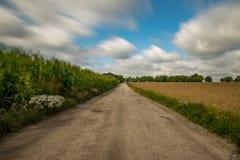 Δρόμος μεταξύ των τομέων καλαμποκιού και των λιβαδιών Στοκ εικόνες με δικαίωμα ελεύθερης χρήσης