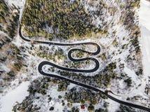 Δρόμος με πολλ'ες στροφές από το πέρασμα υψηλών βουνών, στο χειμώνα Εναέρια άποψη από τον κηφήνα Στοκ εικόνες με δικαίωμα ελεύθερης χρήσης