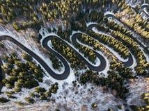 Δρόμος με πολλ'ες στροφές από το πέρασμα υψηλών βουνών, στο χειμώνα Εναέρια άποψη από τον κηφήνα Στοκ Εικόνες