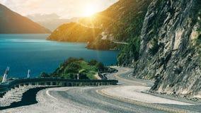 Δρόμος με πολλ'ες στροφές κατά μήκος του απότομου βράχου και της λίμνης βουνών στοκ εικόνες