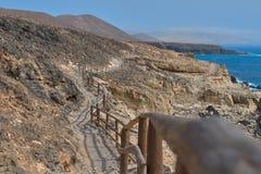 Δρόμος με το ξύλινο κιγκλίδωμα που οριοθετεί την μπλε θάλασσα σε Ajuy, Fuerteventura στοκ εικόνες