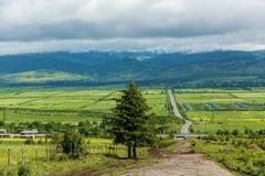 Δρόμος πέρα από το λιβάδι στα βουνά υποβάθρου και το νεφελώδη ουρανό Στοκ εικόνα με δικαίωμα ελεύθερης χρήσης