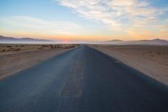 Δρόμος που διασχίζει την έρημο Namib, στο θαυμάσιο εθνικό πάρκο Namib Naukluft, προορισμός ταξιδιού στη Ναμίμπια, Αφρική Πρωί lig Στοκ Φωτογραφία