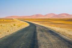Δρόμος που διασχίζει την έρημο Namib, στο θαυμάσιο εθνικό πάρκο Namib Naukluft, προορισμός ταξιδιού στη Ναμίμπια, Αφρική Πρωί lig Στοκ Εικόνες