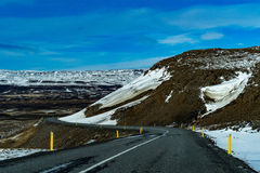 Δρόμος που οδηγεί αν και βουνά το χειμώνα Στοκ Εικόνες