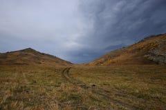 Δρόμος στα βουνά και τα σύννεφα ουρανού Στοκ Εικόνες