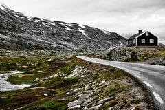 Δρόμος στη Νορβηγία με το σπίτι και το χιονισμένο βουνό Στοκ Φωτογραφίες