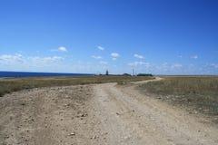 Δρόμος στη στέπα κάτω από τα μπλε σύννεφα skyand στη θάλασσα Στοκ φωτογραφία με δικαίωμα ελεύθερης χρήσης