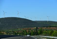 Δρόμος στο τοπίο βουνών Δρόμος ασφάλτου και ανεμοστρόβιλοι στο μπλε ουρανό Κατεύθυνση και προορισμός εναλλακτική ενέργεια στοκ εικόνες