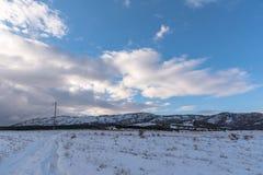 Δρόμος στο χιονώδες βουνό μπλε νεφελώδης ουρανός Στοκ φωτογραφία με δικαίωμα ελεύθερης χρήσης