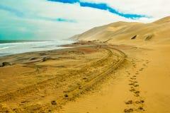 Δρόμος της άμμου μεταξύ του ωκεανού και των αμμόλοφων ερήμων Στοκ εικόνες με δικαίωμα ελεύθερης χρήσης