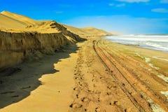 Δρόμος της άμμου μεταξύ του ωκεανού και των αμμόλοφων ερήμων Στοκ φωτογραφία με δικαίωμα ελεύθερης χρήσης