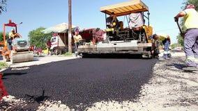 Δρόμος Tarmac που βάζει τη μηχανή στη δραστηριότητα οδοποιίας Οι εργαζόμενοι είναι ισοπέδωση, καθορίζοντας την άσφαλτο φιλμ μικρού μήκους